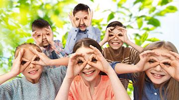 Mehrere Kinder halten sich ihre Hände wie eine Brille vor die Augen.
