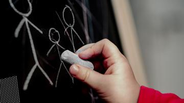 Eine Kinderhand malt Strichmännchen auf eine Tafel.