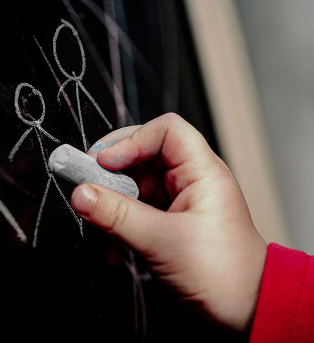 Eine Hand zeichnet mit einem Stück Kreide Strichmännchen an eine Tafel.
