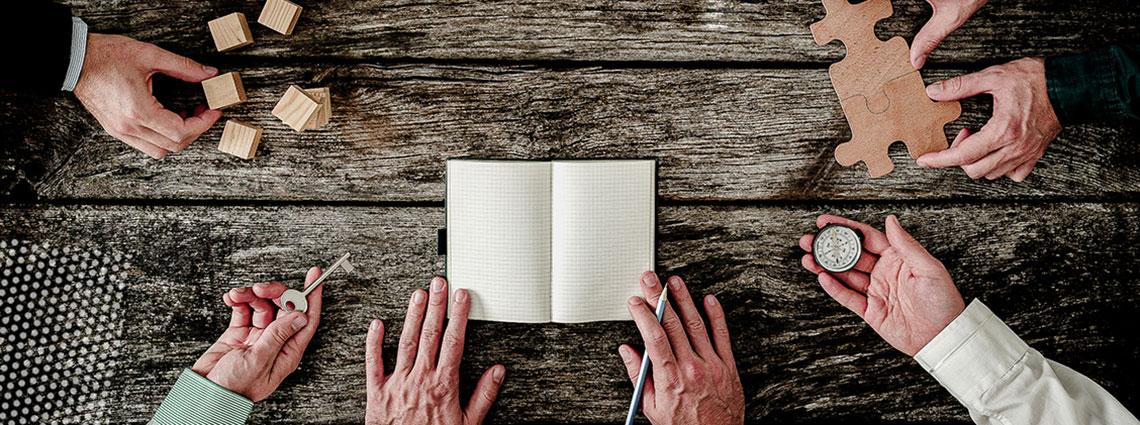 Hände verschiedener Personen legen verschiedene Dinge auf einen Tisch: Holzklötze, Schlüssel, Notizbuch, Uhr, Puzzleteile.