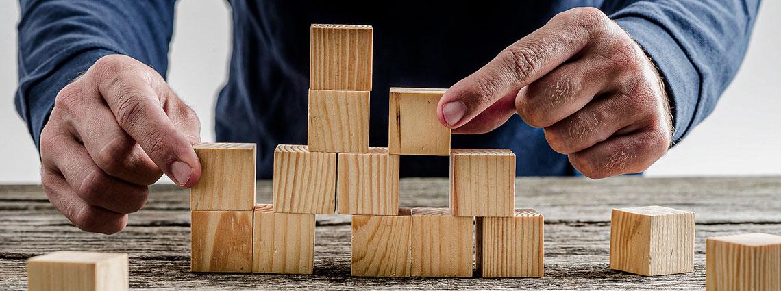 Nahaufnahme: Zwei Hände ordnen mehrere Holzbauklötze neben- und aufeinander an.