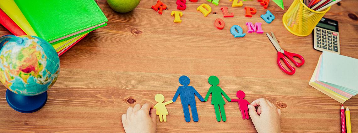 Zwei Hände legen den bunten Scherenschnitt einer Familie auf einen Holzschreibtisch mit Schreibtischutensilien.