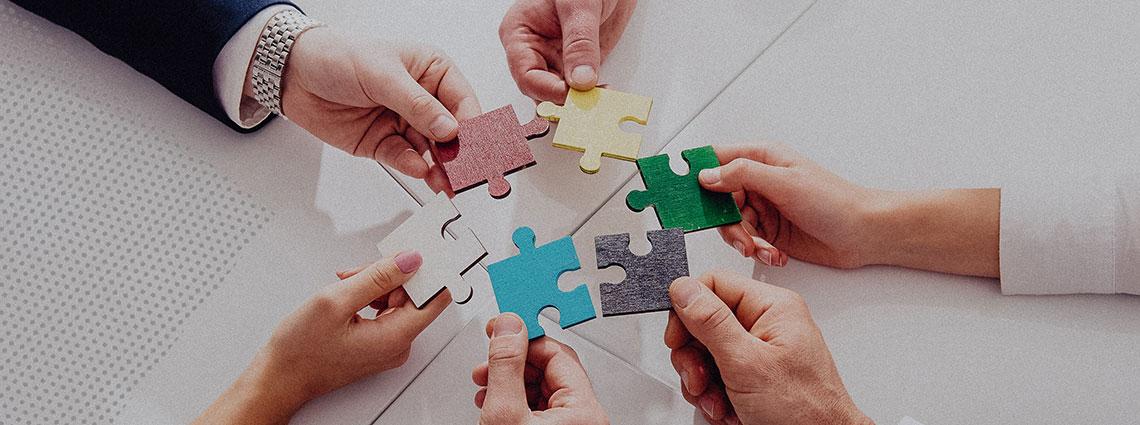 Sechs Hände halten jeweils ein buntes Puzzleteil im Kreis.