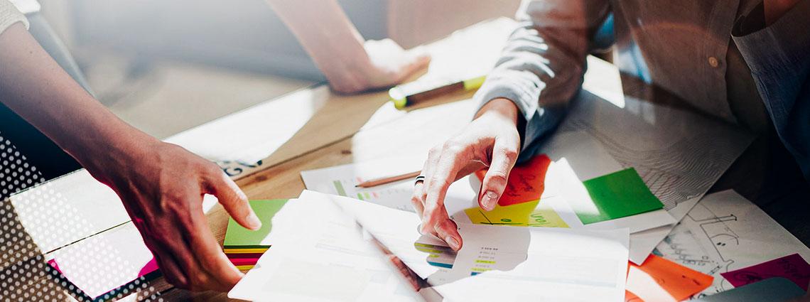 Hände von zwei Personen greifen nach Papieren mit Notizzetteln, die auf einem Tisch verteilt sind.
