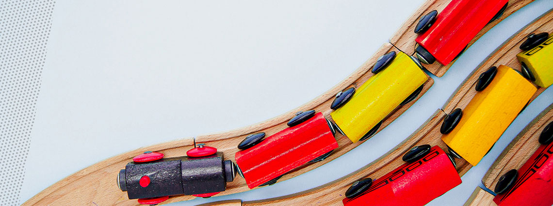 Vogelperspektive: Eine bunte Holzeisenbahn schlängelt sich über ein Holzgleis.
