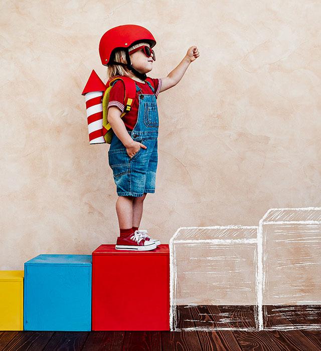 Kind mit Helm und Raketen-Rucksack steht auf einer bunten Treppe. Die folgenden Stufen sind gezeichnet.